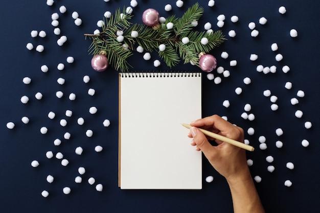 Schreibhand, leeres notizbuch aus papier und weihnachtsdekoration