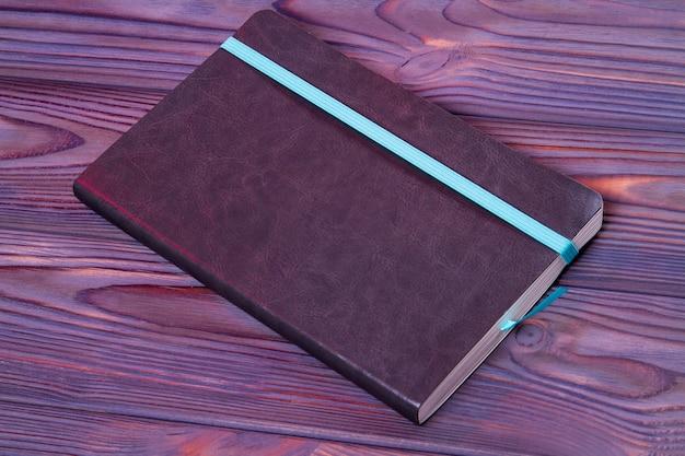 Schreibheft mit ledereinband und blauem lesezeichen. dunkler holzhintergrund.
