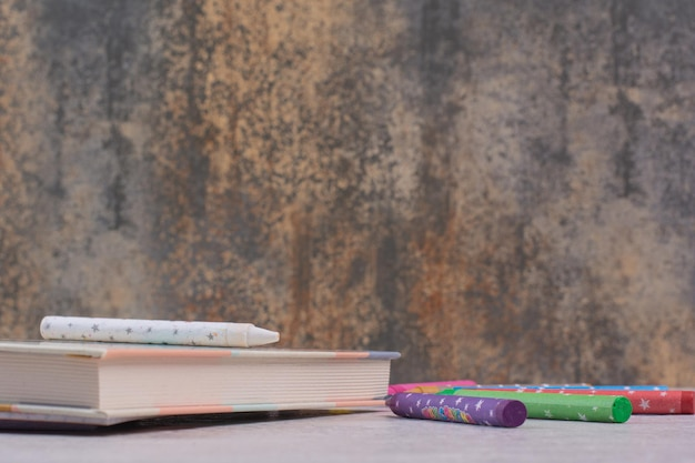 Schreibheft und bunte bleistifte auf weißem tisch.