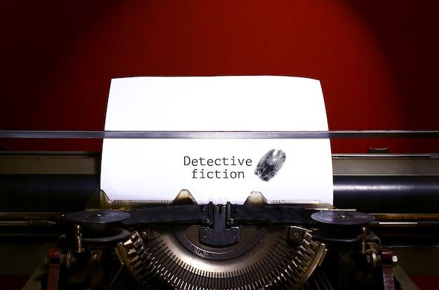 Schreibmaschinenbuchstabier-detektivroman auf papier mit fingerabdruck.