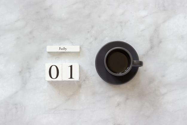 Schreibtisch am büro oder zu hause. holzwürfelkalender 1. juli und tasse kaffee auf marmorhintergrund konzept stilvoller arbeitsplatz