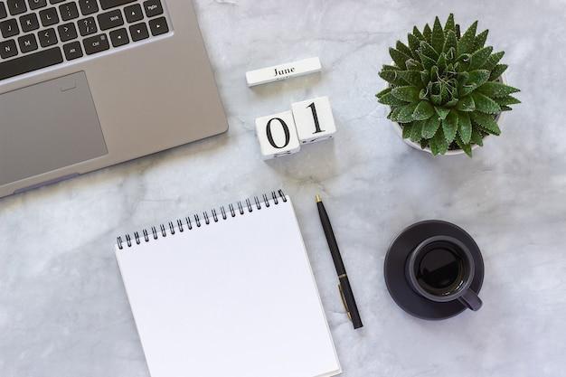 Schreibtisch am büro oder zu hause. holzwürfelkalender 1. juni. grauer laptop, notizblock, tasse kaffee, saftig auf marmorhintergrund