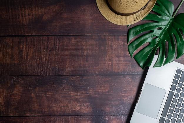 Schreibtisch aus holz mit laptop- und blatt- und blumen-bürobedarf und kopierraum
