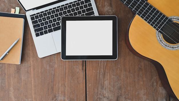 Schreibtisch des songwriters. die draufsicht auf notiz, bleistift, laptop, weißes tablet mit leerem bildschirm und akustikgitarre wird auf den holzschreibtisch gelegt.