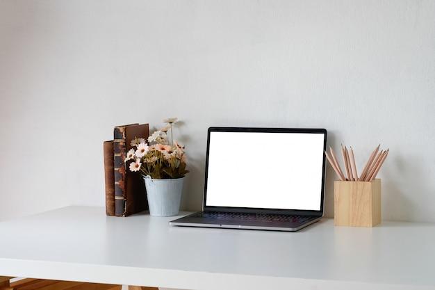 Schreibtisch ein arbeitsplatz mit laptop, büchern, blume und bleistift. montage-bildschirm.