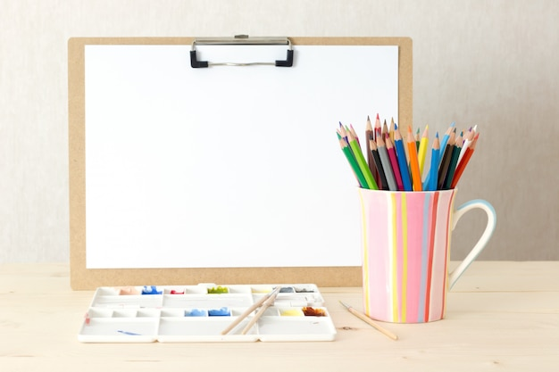 Schreibtisch eines künstlers mit zeichenbrett-lose briefpapiergegenständen. atelieraufnahme auf hölzernem hintergrund.