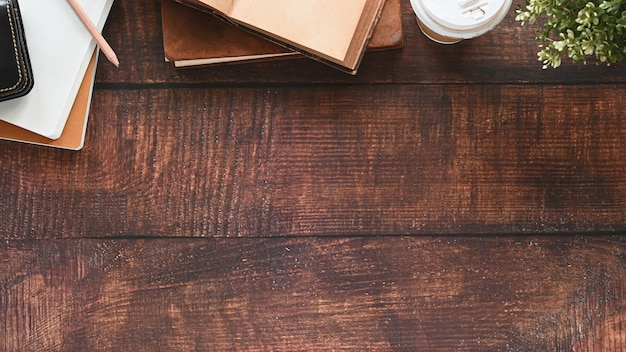 Schreibtisch holztisch mit buch, bleistift, kaffeetasse, topfpflanze und notizbuch.