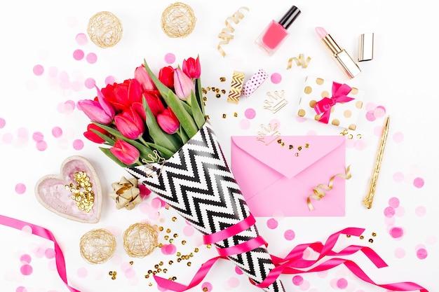 Schreibtisch im rosa-goldenen stil mit floralen rosa tulpen-kosmetika und weiblichen accessoires