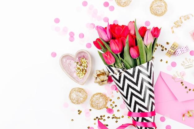 Schreibtisch in rosa und gold mit blumenmuster. rosa tulpen in schwarz-weißem stilvollem geschenkpapier, geschenken, kosmetik und weiblichen accessoires mit konfetti auf weißem hintergrund