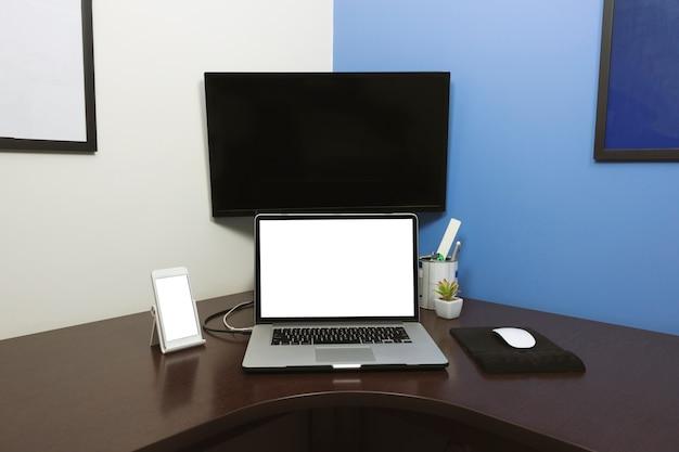 Schreibtisch laptop und handy mit leerem textraum bildschirm im büro auf holztisch
