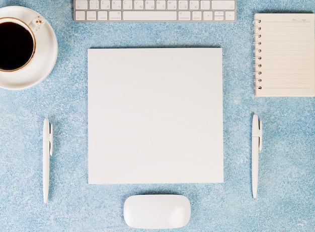 Schreibtisch mit arbeitsmaterial, maus, tastatur, kaffeetasse und notizblock. draufsicht, flatley.