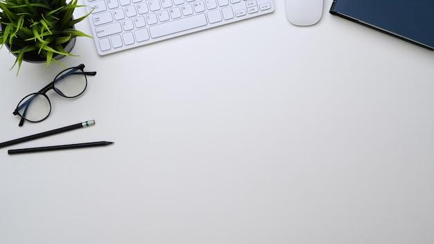 Schreibtisch mit brille, tastatur, stiften, pflanzen- und kopierraum auf weißem hintergrund.