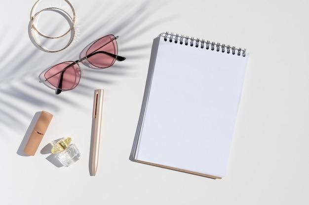 Schreibtisch mit damenaccessoires, geöffnetem spiralblock und palmblattschatten