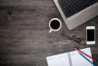 Schreibtisch mit einem Laptop, einer Tasse Kaffee und einem Kalender