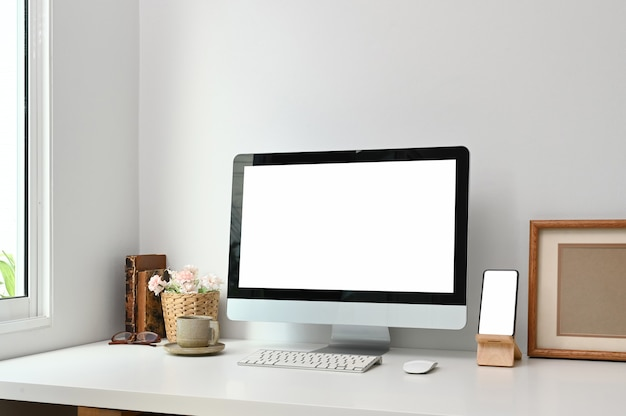 Schreibtisch mit einem modellcomputer und einem smartphone auf weißem tisch