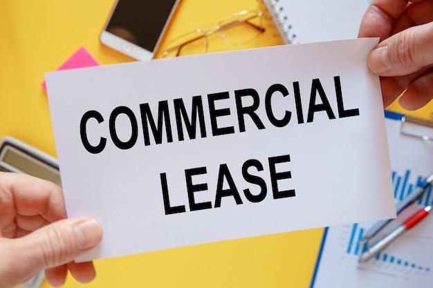 Schreibtisch mit elektronischen geräten und dokumenten, commercial lease-beschriftung auf papier.