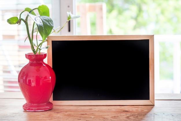 Schreibtisch mit freiem raum mit grüner pflanze und fenster der frühlingszeit