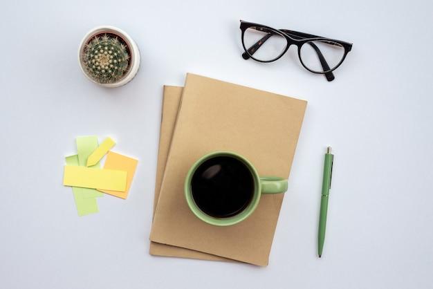 Schreibtisch mit gläsern, tasse kaffee auf einem notizbuch stehend - draufsicht