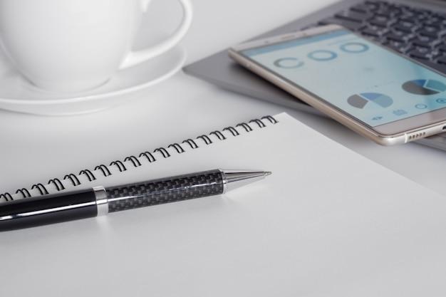 Schreibtisch mit handy mit unternehmensanalysediagramm