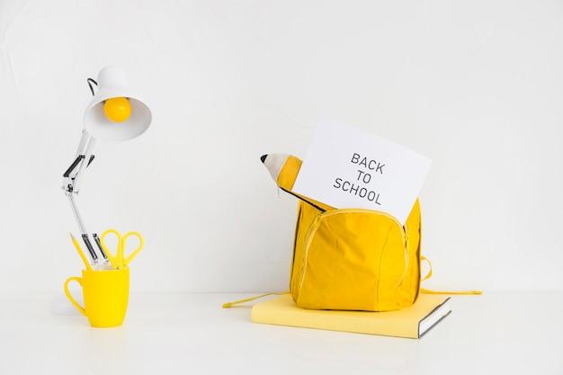 Schreibtisch mit hellem gelbem rucksack und federmäppchen