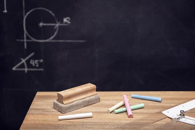 Schreibtisch mit kreide, radiergummi und tafel mit geometriezeichnungen