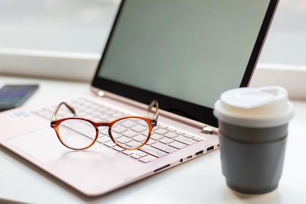 Schreibtisch mit laptop, augengläsern und einer tasse kaffee. konzept des geschäfts