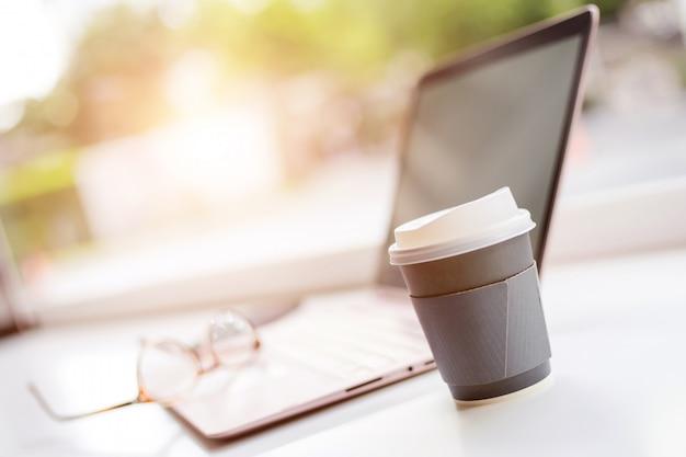 Schreibtisch mit laptop, brille und einer tasse kaffee