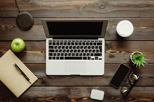 Schreibtisch mit laptop-computer, versorgungen und grünem apfel, draufsicht