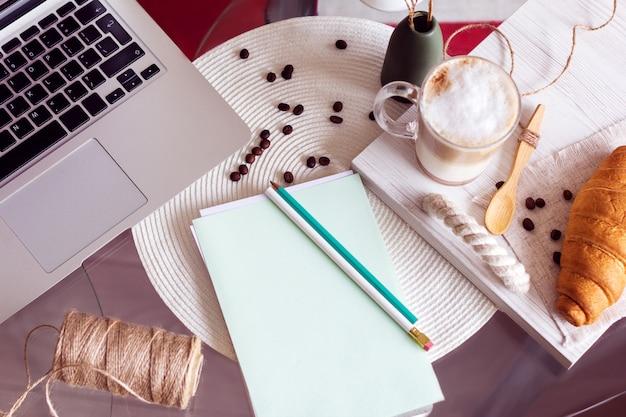 Schreibtisch mit laptop, kaffee und croissant