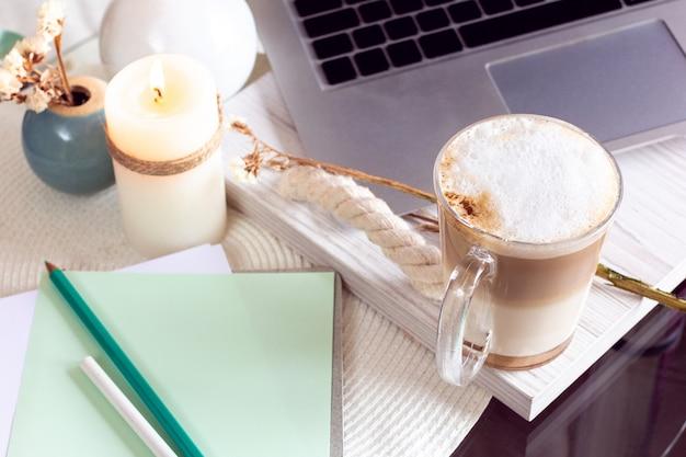 Schreibtisch mit laptop, kaffee und kerze