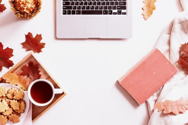 Schreibtisch mit laptop, kaffeetasse, keksen, buch und herbstlaub. draufsicht