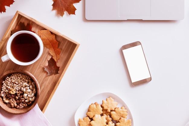 Schreibtisch mit laptop, kaffeetasse, keksen, smartphone und herbstlaub. draufsicht