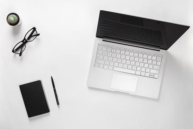 Schreibtisch mit laptop, kaktus, brille, notizbuch und stift