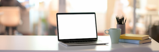 Schreibtisch mit laptop mit leerem bildschirm, schreibwaren, kaffeetasse und kopierraum im trennraum aus glas