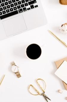 Schreibtisch mit laptop- und frauenzubehörsammlung und baumwollzweig auf weißem hintergrund. ansicht von oben.