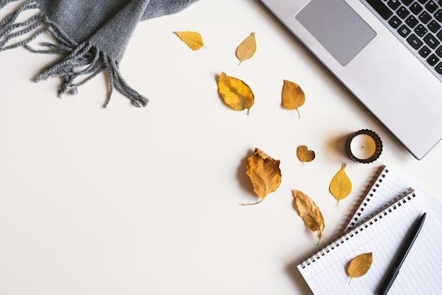 Schreibtisch mit laptopkerzennotizbüchern, stiftdecke und kleinen getrockneten blättern herbstsaison