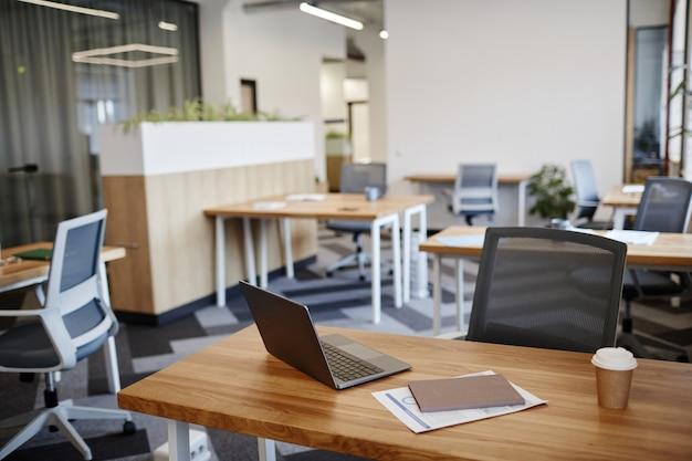 Schreibtisch mit laptoptasse kaffee und bericht im leeren büro im modernen gebäude