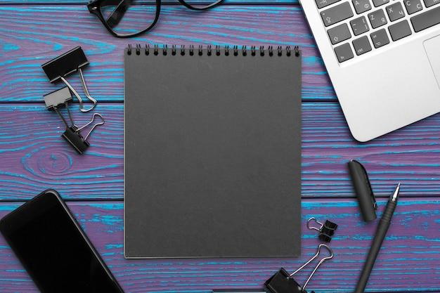 Schreibtisch mit leerem notizblock, laptop und draufsicht des büroartikels