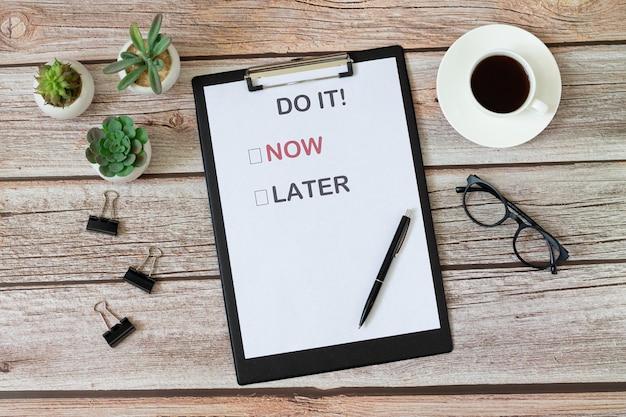 Schreibtisch mit motivationsplakat draufsicht. wählen sie, ob sie es jetzt oder später tun möchten