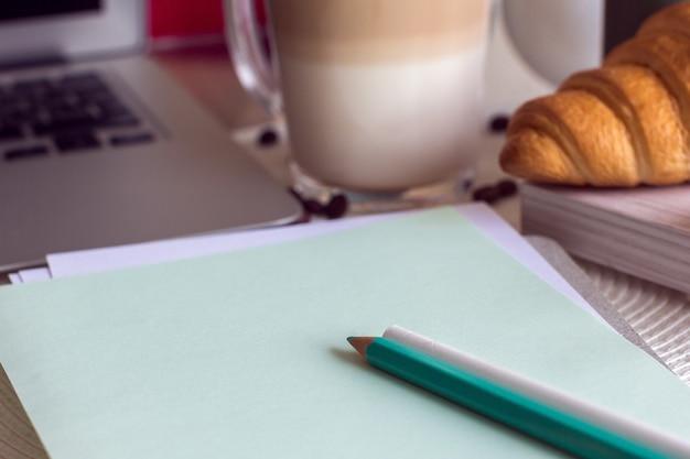 Schreibtisch mit notebook, laptop, kaffee und croissant