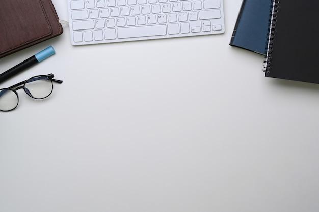 Schreibtisch mit notebook, tastatur, brille und kopierraum.