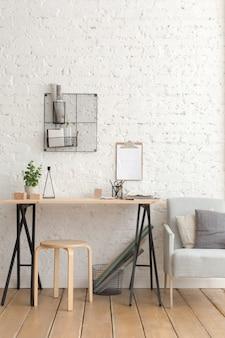 Schreibtisch mit schreibwaren im weißen interieur loft