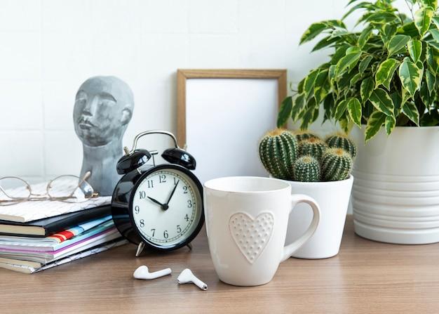 Schreibtisch mit stapel von notizblöcken, wecker, büromaterial und zimmerpflanzen