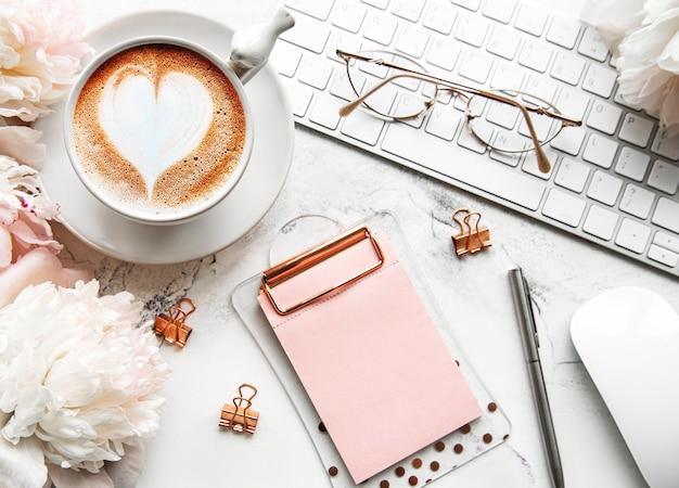 Schreibtisch mit tasse kaffee und pfingstrosenblumen