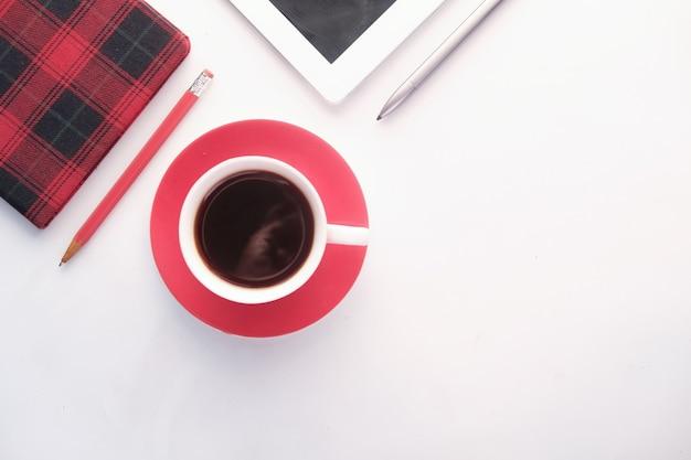 Schreibtisch mit tee, notizblock und digitalem tablet