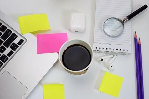 Schreibtisch schwarzer kaffee haftnotizen und laptop