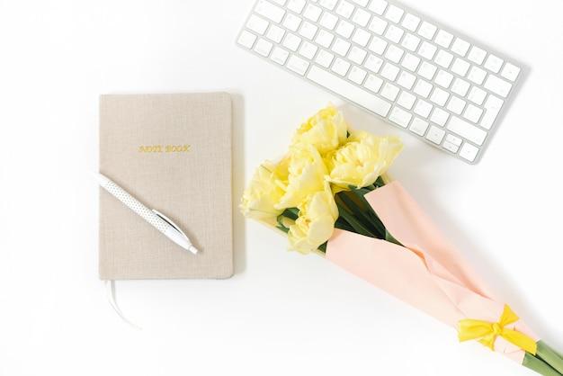 Schreibtisch tisch. flache lage, draufsicht. home-office-arbeitsbereich eines freiberuflers oder bloggers. eine tastatur, ein paar tulpen und ein notizblock mit einem stift.