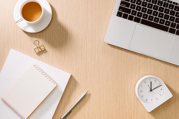 Schreibtisch tisch mit laptop, smartphone, tasse kaffee, stift, bleistift und notizbuch. büromaterial und geräte auf dem schreibtisch tisch. schreibtisch-tischkonzept.