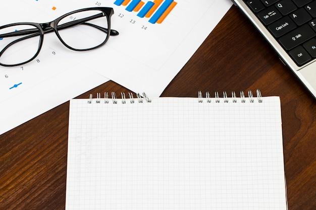 Schreibtisch tisch mit rohling, stift, finanzbericht und tasse kaffee