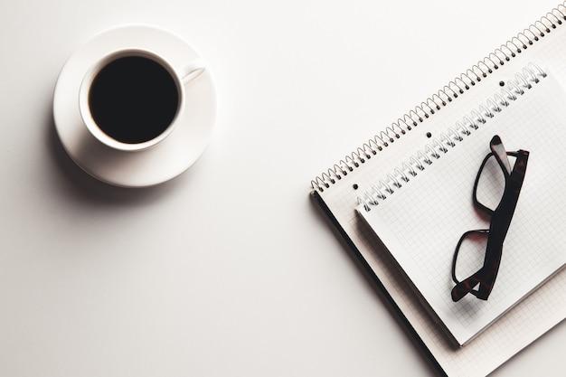 Schreibtisch tisch mit zubehör, kaffeetasse und blume. draufsicht mit kopierraum